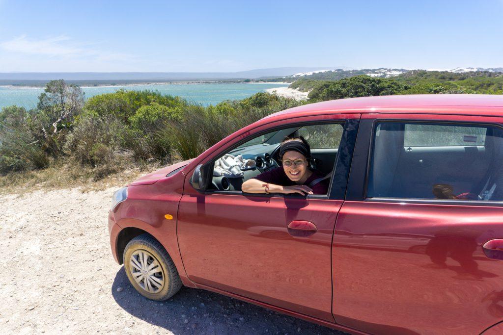 Garden Route Südafrika - Sara schaut aus dem Fenster ihres roten Mietwagens.