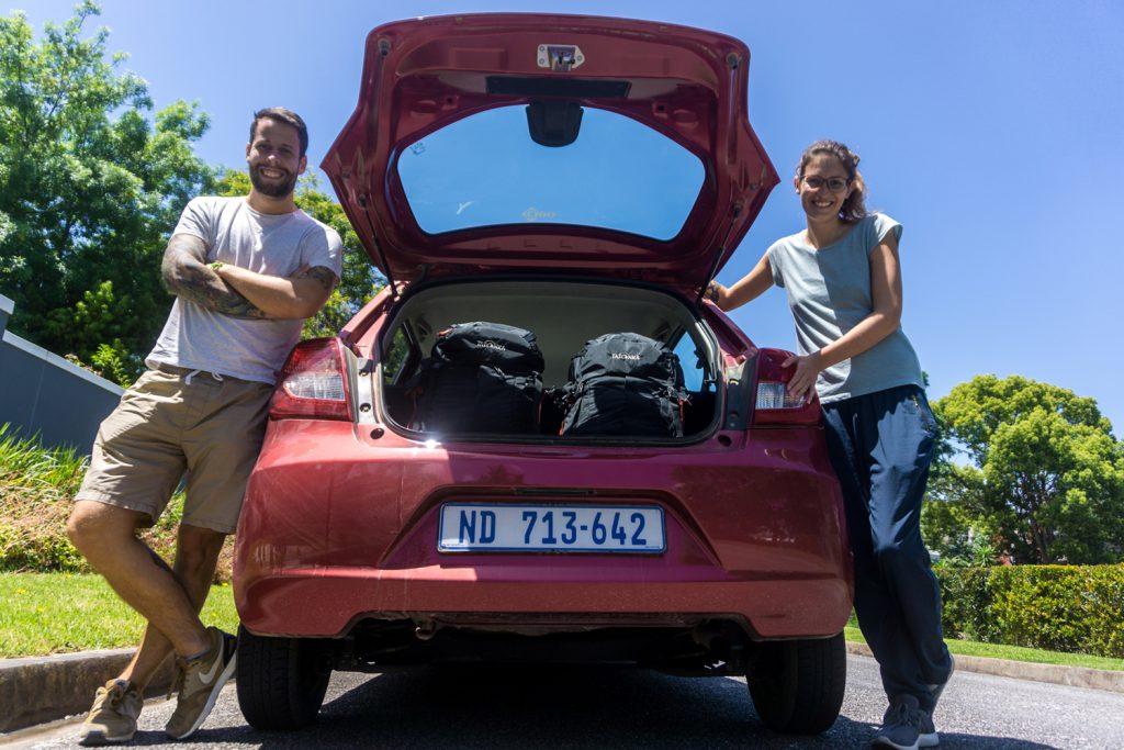 Garden Route Südafrika - Sara und Marco vor dem offenen Kofferraum ihres roten Mietwagens.