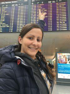 Auf dem Weg zum Roadtrip Yucatan - Sophie zeigt am Flughafen München auf die Anzeigentafel. Es geht nach Mexiko.