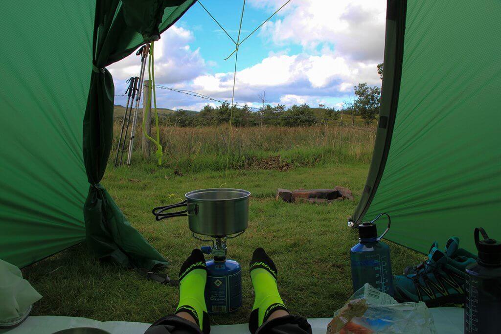 Julia streckt ihre Füsse aus dem Zelt. Vor ihr sind bereits Gaskocher und Topf aufgebaut.