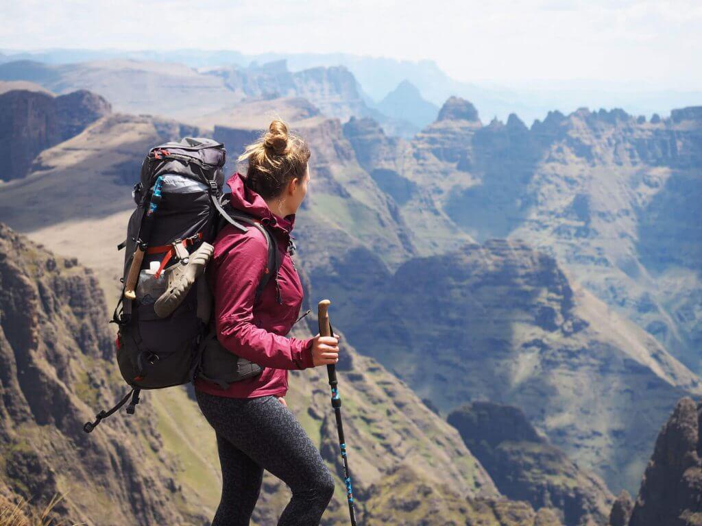 Trekken durch die Drakensberge - Kathrin Heckmann steht an der Abbruchkante und blickt auf die Berglandschaft.