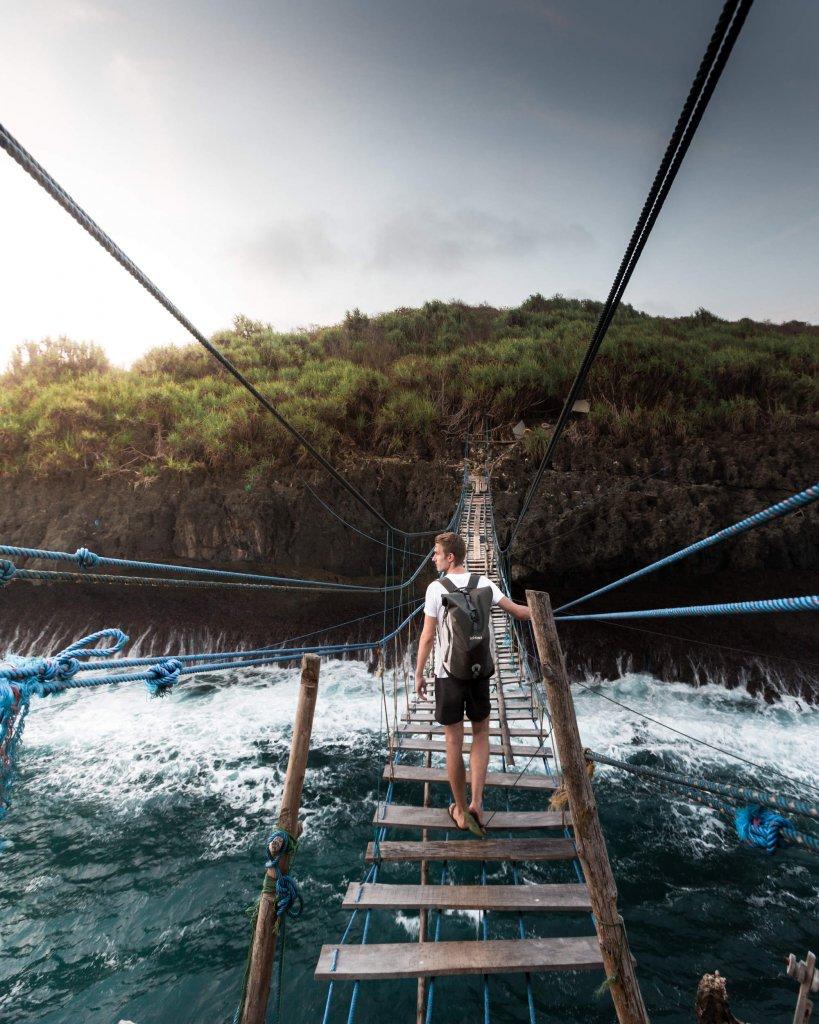 Hängebrücke zu einer Fischerinsel im Süden von Java, Indonesien.