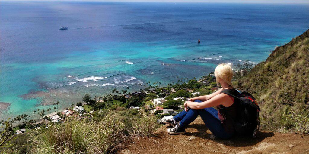 Nicole blickt von einer Klippe in Waikiki, Hawaii aufs Meer.