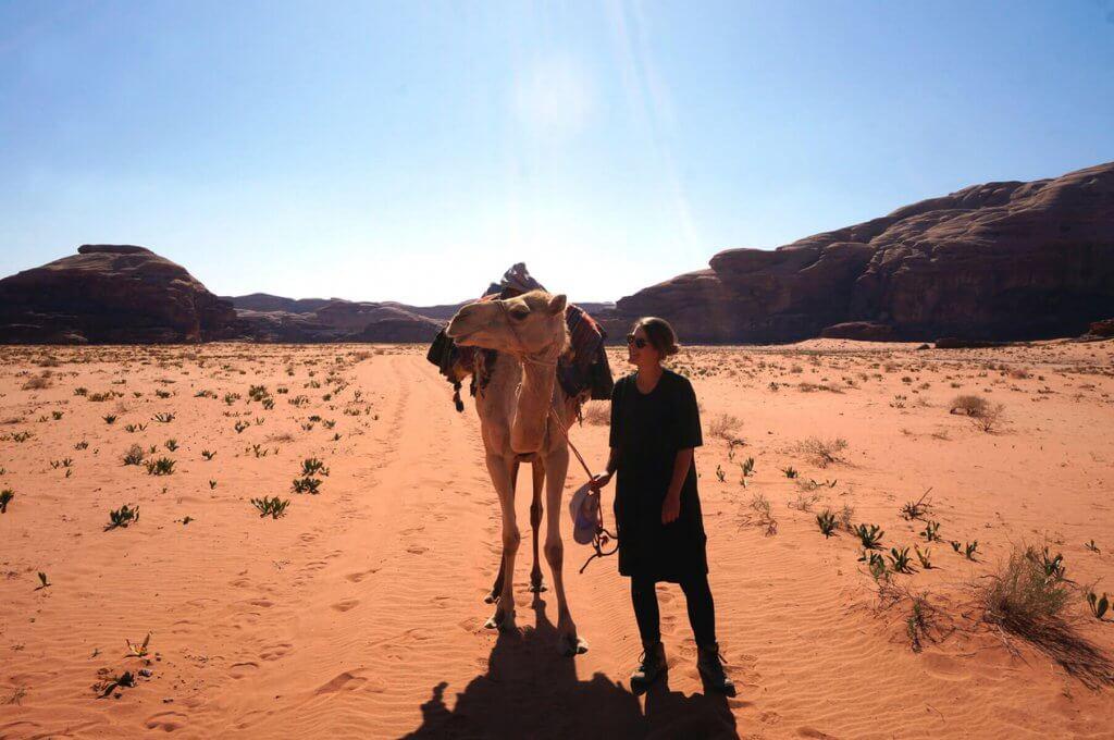 Jennifer mit einem Kamel auf einer Wanderung durch das Wadi Rum in Jordanien.