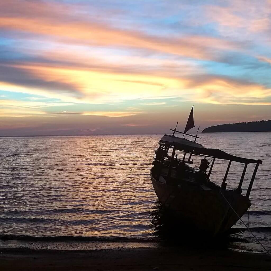 Boot im Sonnenuntergang an einem Strand in Kambodscha.