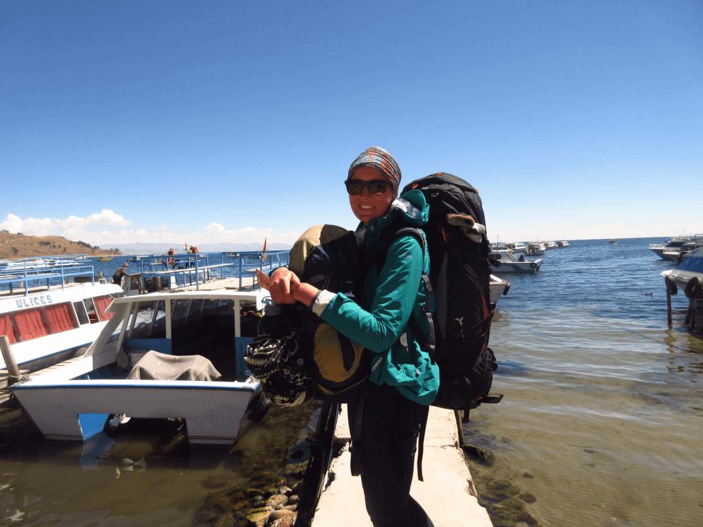 Melissa mit ihrem Rucksack morgens in Cobacabana am Titicacasee in Bolivien.