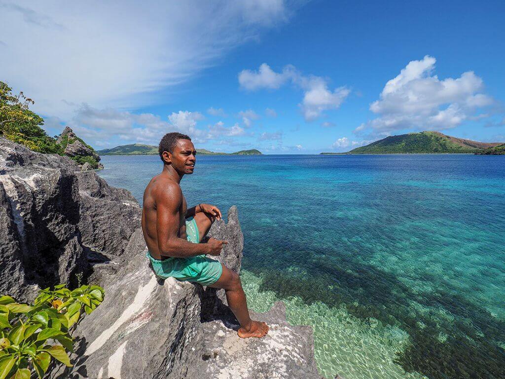 Reise auf die Fidschi-Inseln - Ein Einheimischer sitzt auf einem Felsen und blickt aufs Meer.