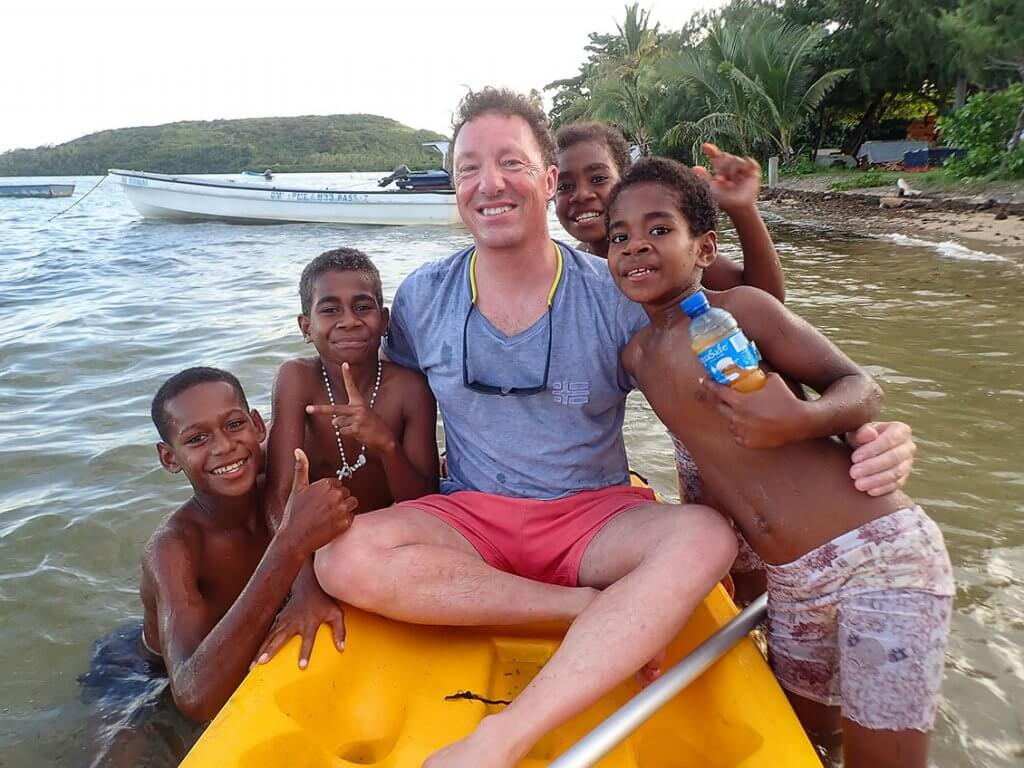 Michi Bösiger auf einem Kanu umringt von Kindern auf den Fidschi-Inseln.