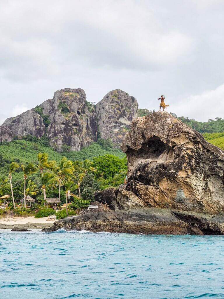 Reise zu den Fidschi-Inseln - Ein Krieger mit Lendenschutz auf einem Felsen.
