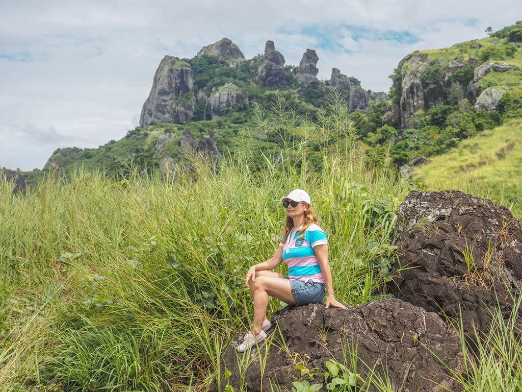Caroline sitzt auf Matacawalevu-Island auf einem kleinen Felsen.