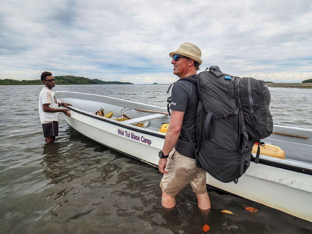 Michi Boesiger mit seinem Reiserucksack auf dem Rücken vor einem Motorboot.