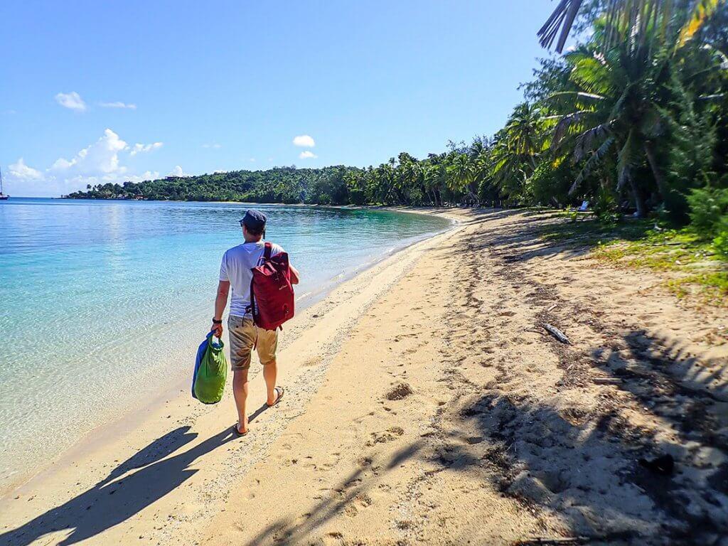 Michi Bösiger läuft mit seinem Rucksack einen Sandstrand auf den Fidschi-Inseln entlang.
