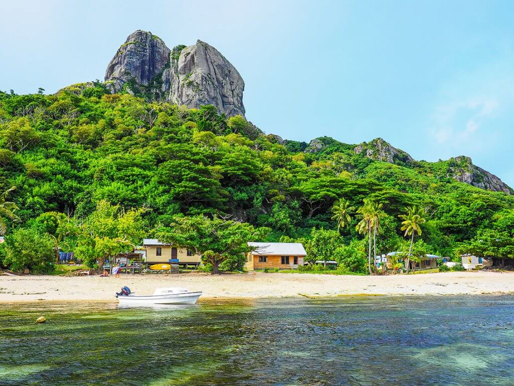 Reise auf die Fidschi-Inseln - Strand mit Bäumen und Berg.