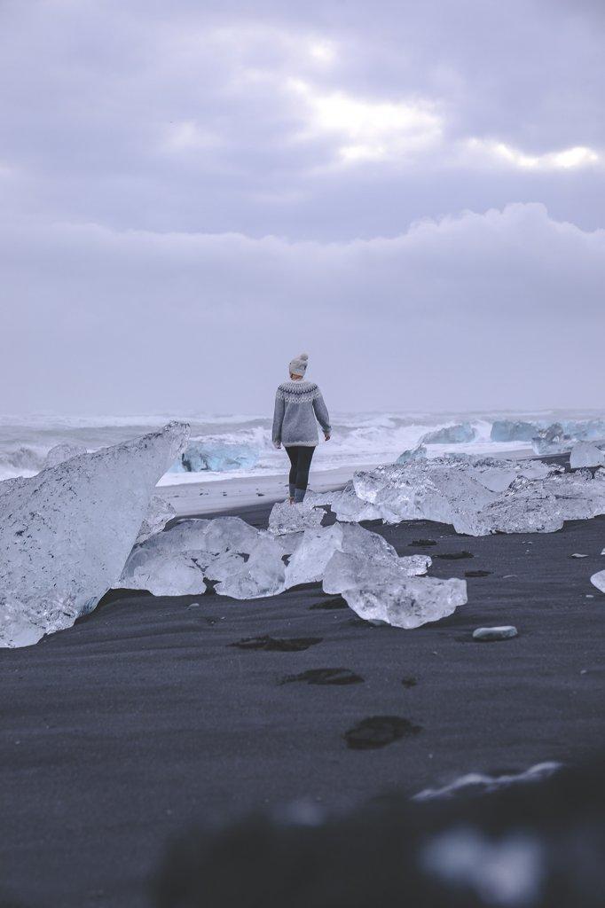 Line zwischen Eis und schwarzem Sandstrand an der Gletscherlagune Jökulsárlón auf Island.
