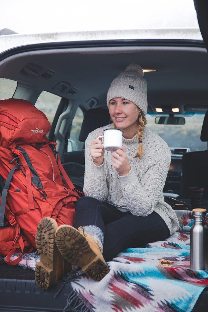 Line genießt eine Tasse Kaffee in ihrem Van während ihres Roadtrips durch Island.
