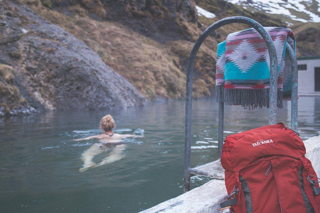 Line nimmt ein Bad im Seljavallalaug Schwimmbad.