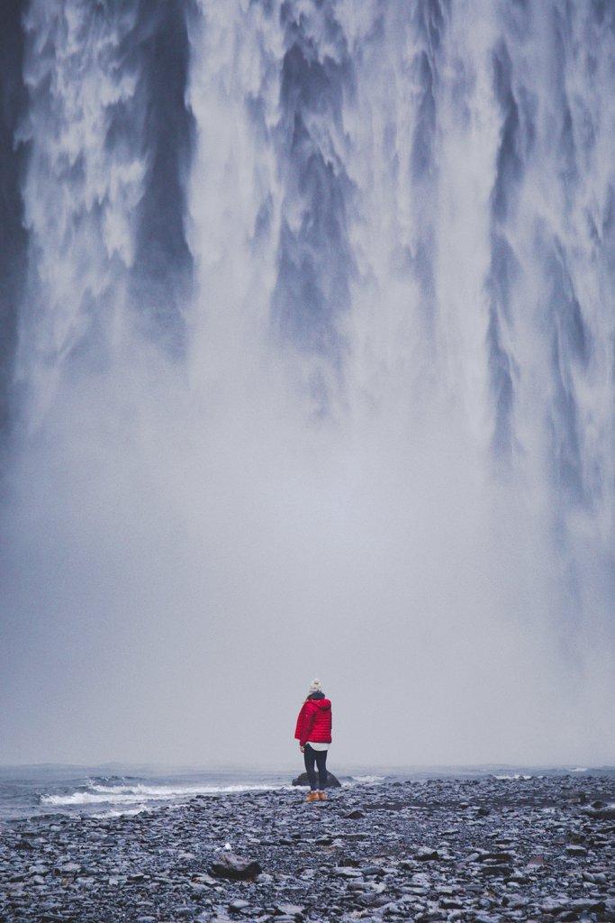 Line steht vor dem ca. 60 Meter hohen Skogafoss Wasserfall in Island.