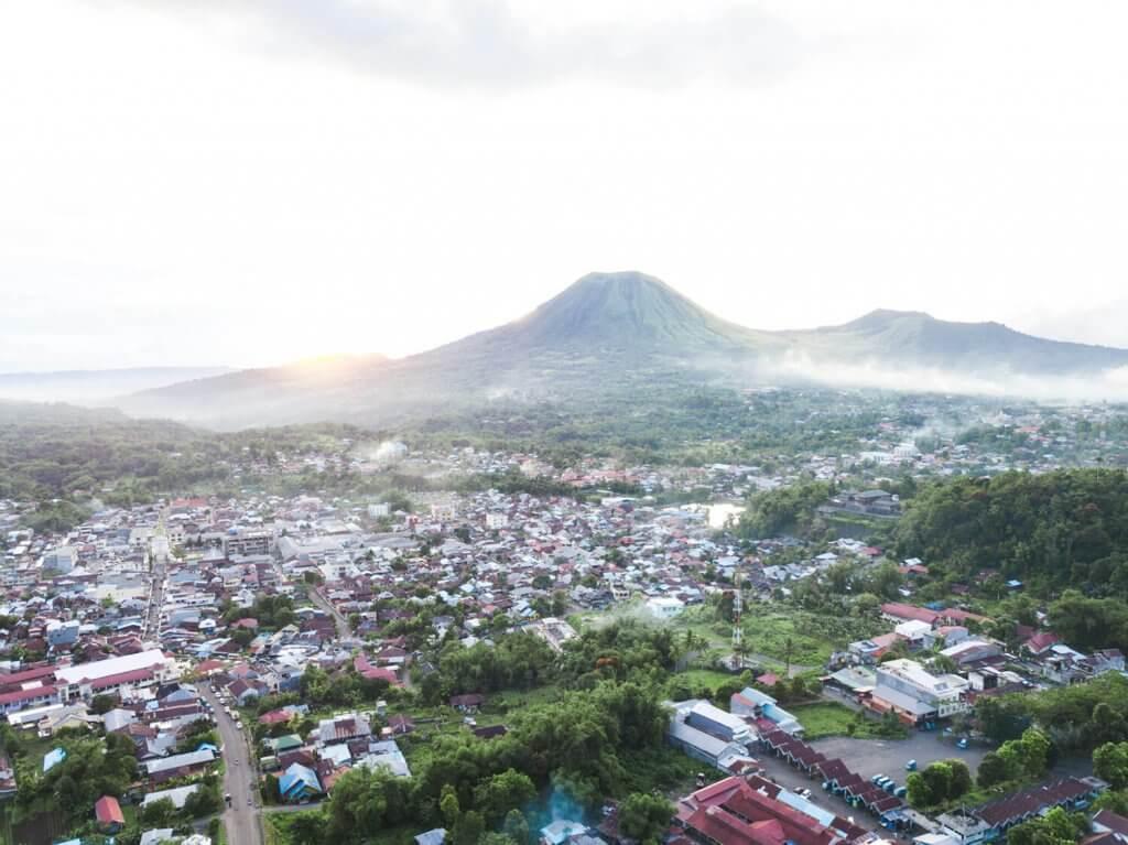 Rundreise Sulawesi - Blick auf die Stadt Tomohon mit dem aktiven Vulkan Lokon.