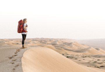 Für die Tatonka Trekkin' Crew besuchte Marko Roth den Oman. Reisebegleitung Joanna steht mit dem Yukon Trekkingrucksack auf einer Sanddüne in der Wüste.