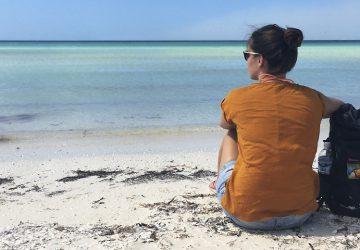 The Trekkin' Crew in Yucatan, Mexiko - Sophie sitzt am Strand und genießt das Rauschen des Meeres.