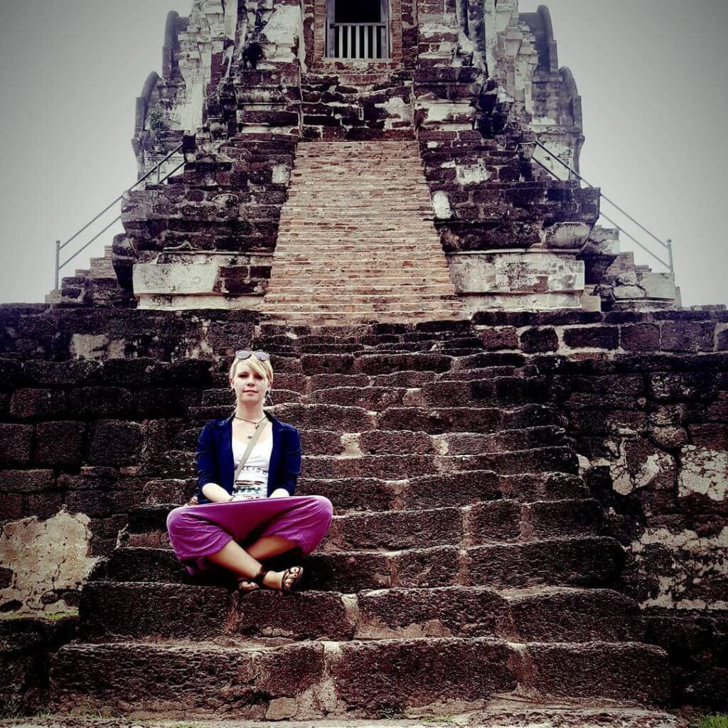 Nicole sitzt auf einer Stufe der Tempelruine Ayutthaya in Thailand.