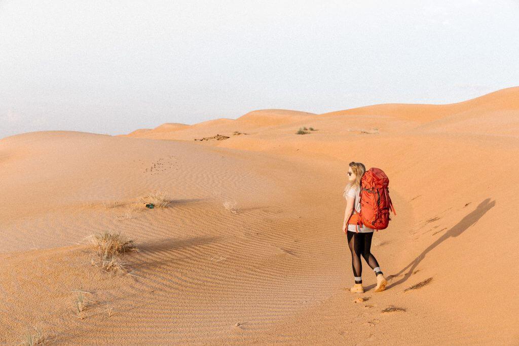 Joanna mit ihrem Tatonka Yukon Trekkingrucksack auf dem Rücken in der Wahiba Sands Wüste im Oman.