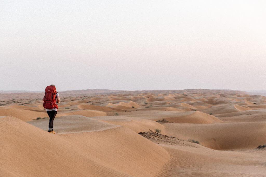 Joanna mit ihrem Tatonka Yukon Trekkingrucksack auf dem Rücken auf einer Sanddüne in der Wahiba Sands Wüste im Oman.