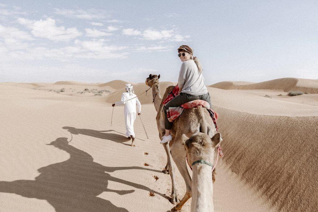 Joanna auf einem Kamel. Ein Beduine führt die Karawane durch die Wahiba Sands Wüste im Oman.