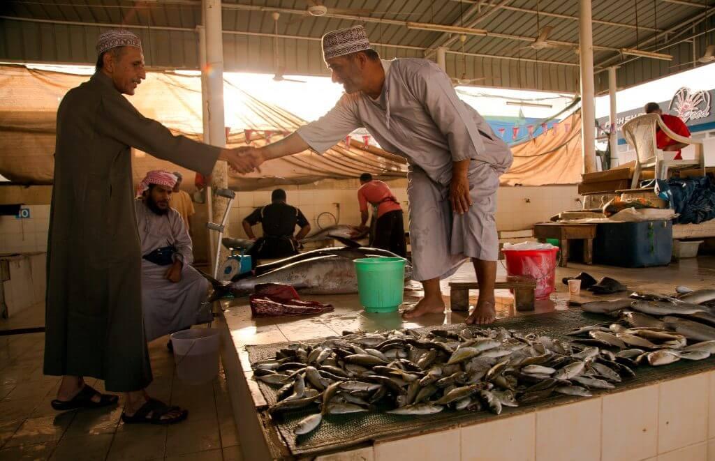 Abgeschlossenes Geschäft? Händler geben sich auf einem Fischmarkt im Oman die Hand.