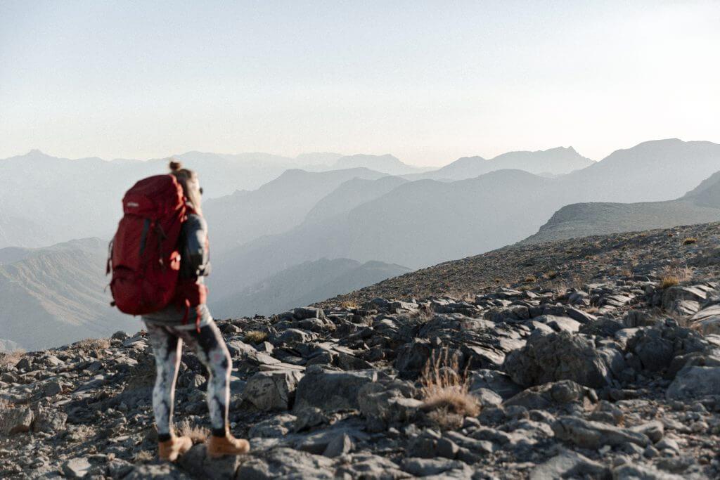 Joanna erkundet mir ihrem Yukon Trekkingrucksack die steinige Berglandschaft von Khasab im Oman.