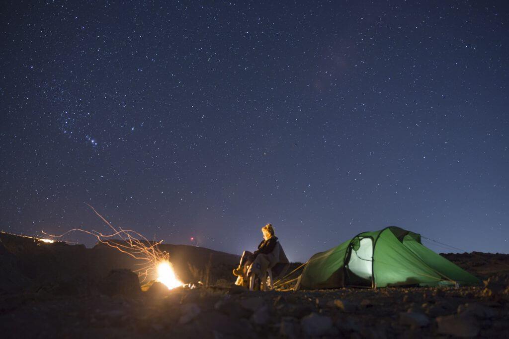 Kristallklarer Sternenhimmel über dem Oman – Joanna wärmt sich am Lagerfeuer vor ihrem Tatonka-Zelt.