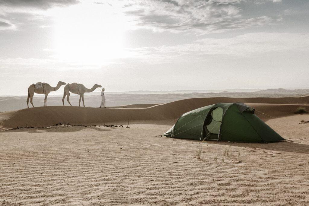 Aufgebautes Tatonka Zelt in der Wahiba Sands Wüste. Im Hintergrund zieht ein Beduine mit zwei Kamelen vorbei.