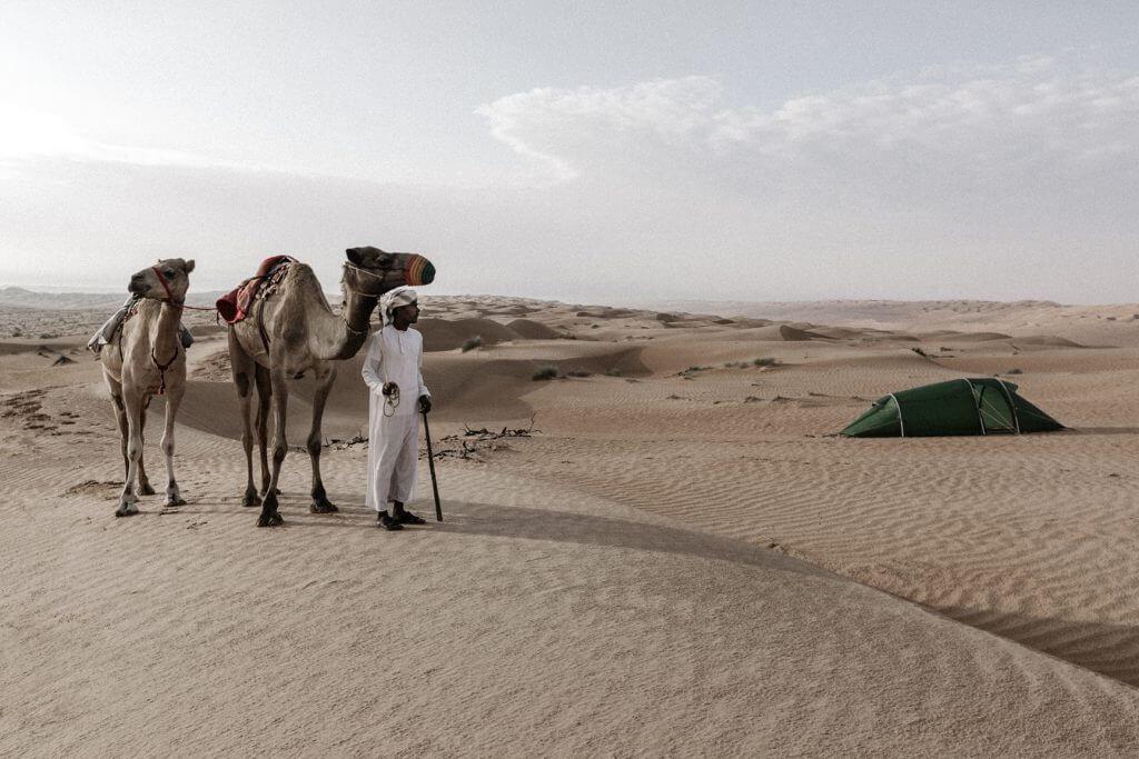 Beduine mit zwei Kamelen im Schlepptau, der auf das aufgebaute Tatonka Zelt schaut.