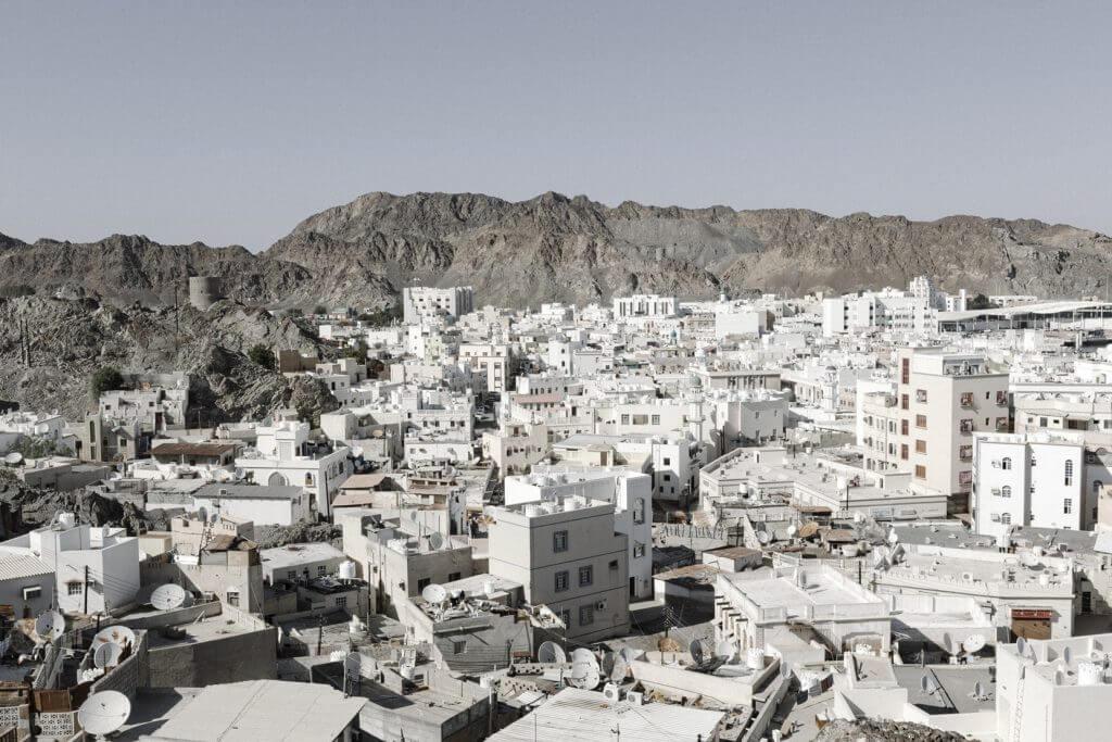 Blick von oben auf die weissen Häuser einer Stadt im Oman.