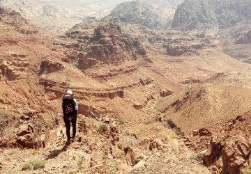 Trekken durch Jordanien - Jennifer blickt auf die karge aber beeindruckende Landschaft nahe Feynan in Jordanien.
