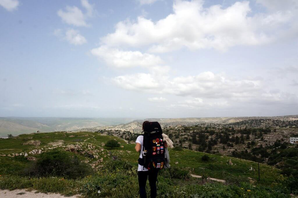 Jennifer blickt auf die gründe Landschaft von Sattgrüne Landschaft des Jordan Trails. Der Weg von Umm Qais nach Adjloun liegt vor ihr.