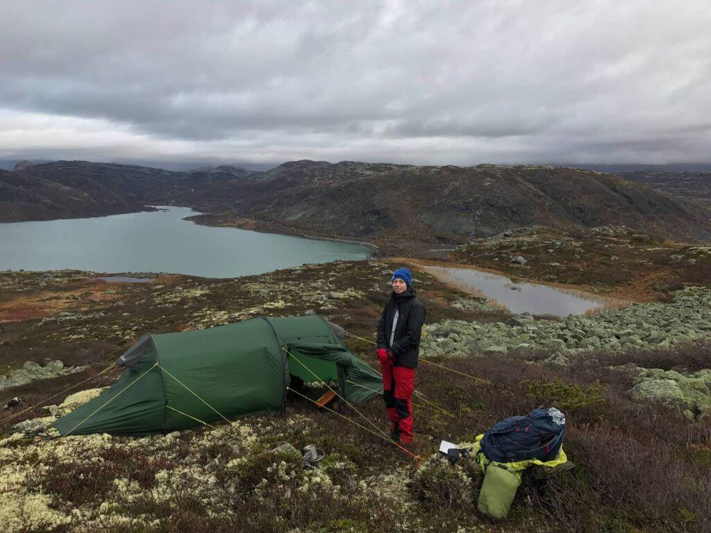 Aufgebautes Tatonka-Zelt auf einem Hochplateau mit See im Hintergrund