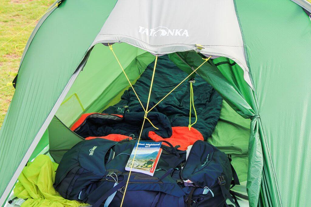 Trekkingrucksack und Wanderführer liegen im Zelt.